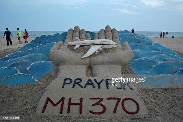 Beachgoers walk past a sand sculpture made by Indian sand artist Sudersan Pattnaik with a message of prayers for the missing Malaysian Airlines...