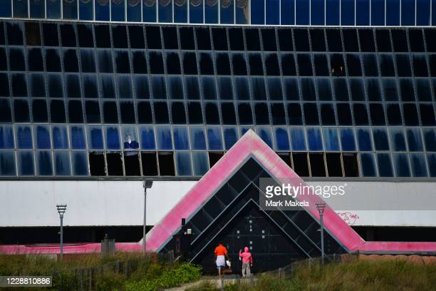 Beachgoers walk towards Trump Plaza Hotel and Casino, once one of the city's premier destinations, now with demolition underway on September 30, 2020...