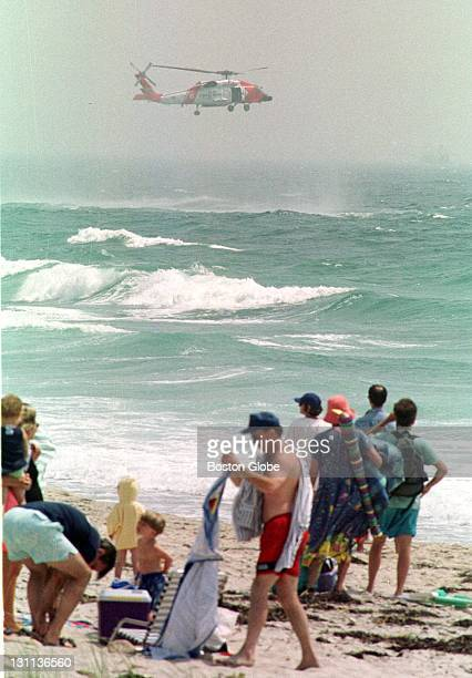 Beachgoers watch as a US Coast Guard rescue helicopter searches along Philbin Beach near Gay Head on the island of Martha's Vineyard Mass Saturday...