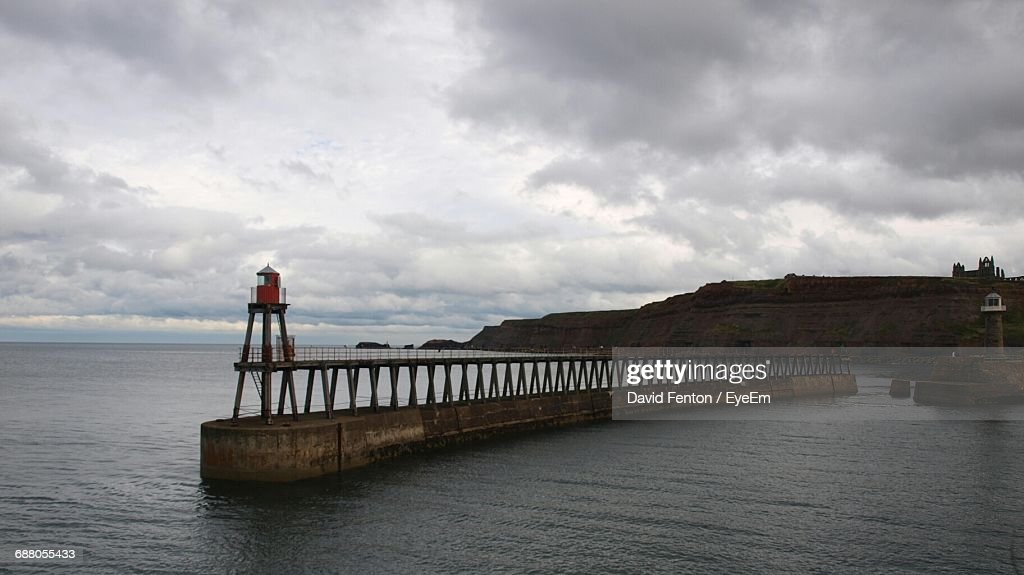 Beacon On Pier In Sea Against Cloudy Sky : Stock Photo
