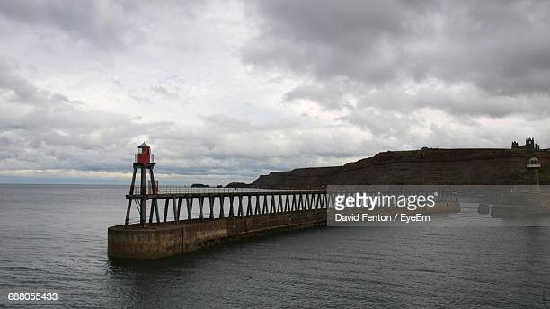beacon on pier in sea against cloudy sky - prudence fenton stock pictures, royalty-free photos & images