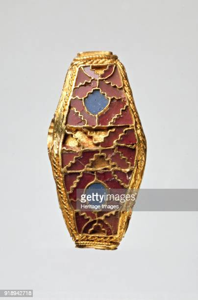 Bead AngloSaxon Period Foursided lentoid bead gold with cloisonne of garnet and blue stone two opposite sides are alike Dimensions length 35 cmwidth...
