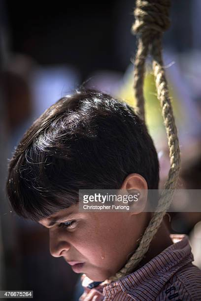 A bead of sweat runs down the cheek of a young palestinian boy wearing a hang mans noose in a symbolic protest against the Bank of Palestine 'hanging...