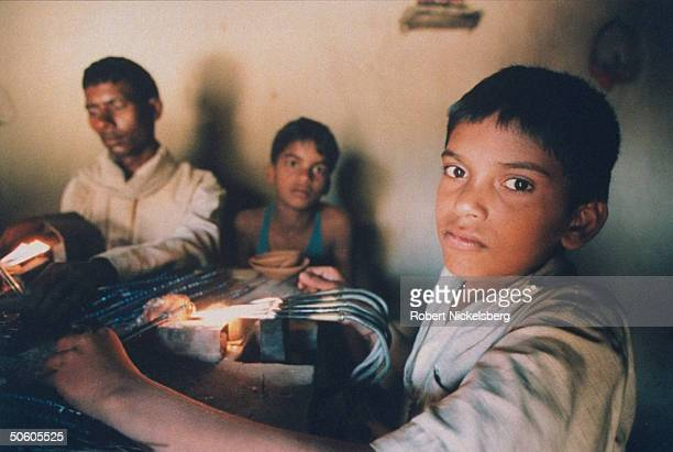 Beadworking family boy working glass rod over gas jet w/o ventilation or protective gloves re exceptional natl prevalence of exploited child labor