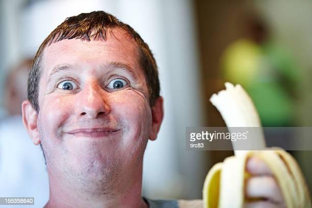 Beady-eyed Mann Essen Banane