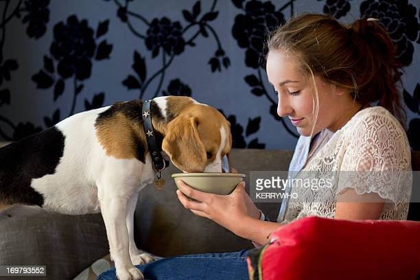 Beagle and teenage girl share from a bowl