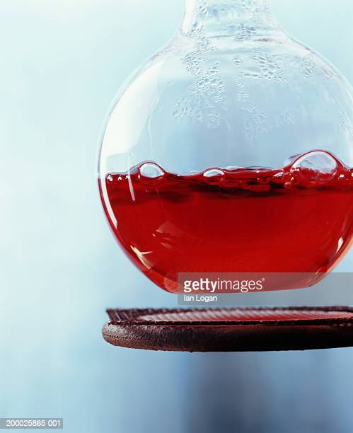 Beaker filled with red liquid suspended above bunsen burner