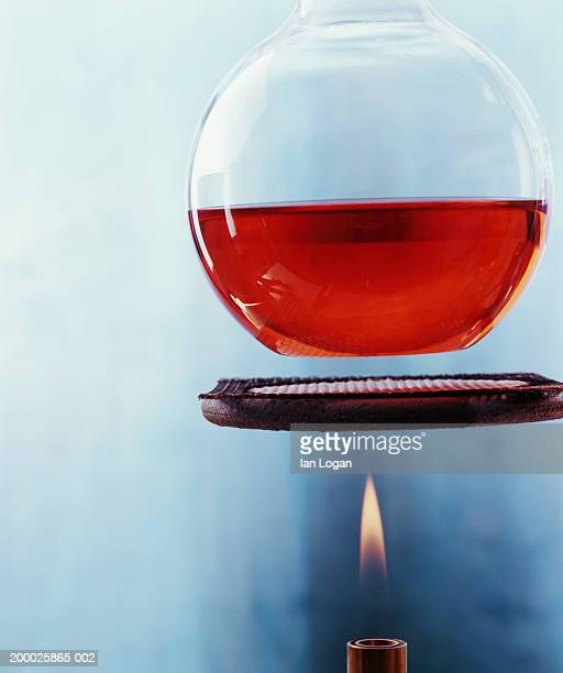 Beaker filled with red liquid suspended over bunsen burner with flame