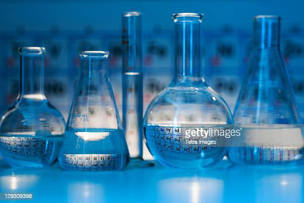 beakers and flasks with periodic tables in laboratory - periodic table stock pictures, royalty-free photos & images