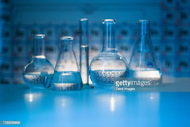 beakers and flasks with periodic tables in laboratory - periodic table stock photos and pictures