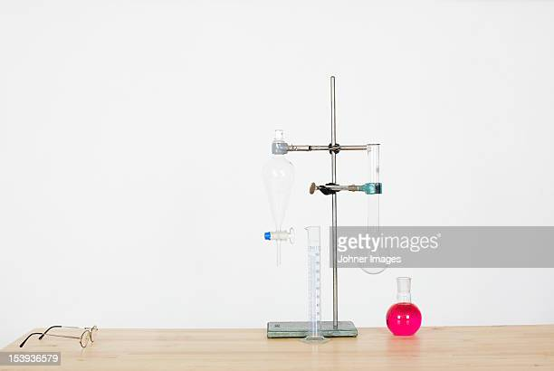 Beakers in stand and eyeglasses on workbench