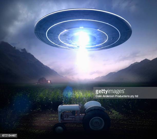 beam from ufo over tractor at farm - spaceship stock photos and pictures