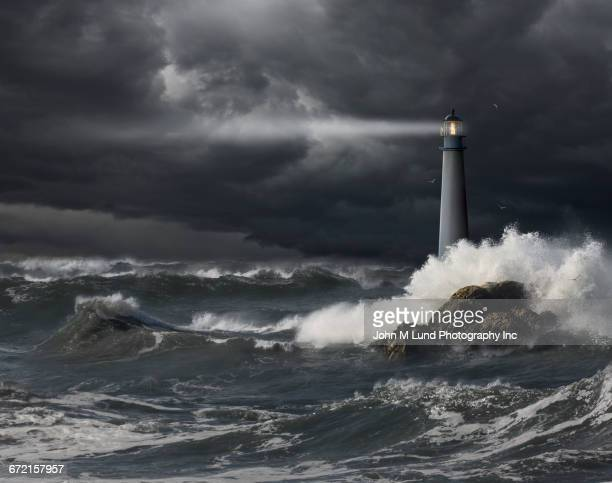 beam of light shining into stormy ocean - leuchtturm stock-fotos und bilder