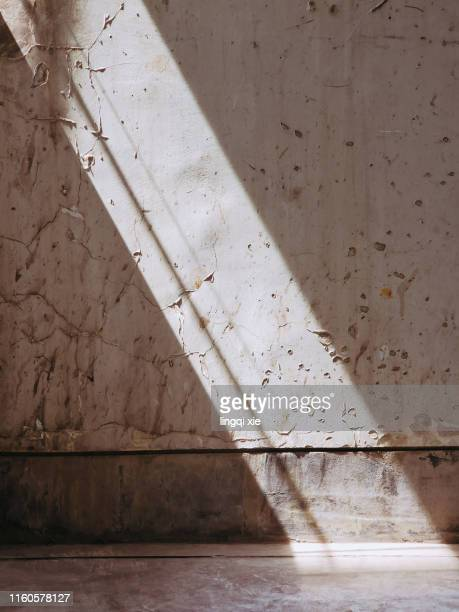 a beam of sunlight illuminated the corner of the wall - sunbeam stock pictures, royalty-free photos & images