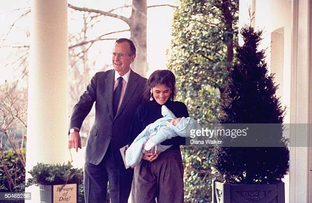 Beaming grandpa Pres Bush standing by beware of dog signbearing planter w babeinarms bearing daughterinlaw Margaret by WH portico