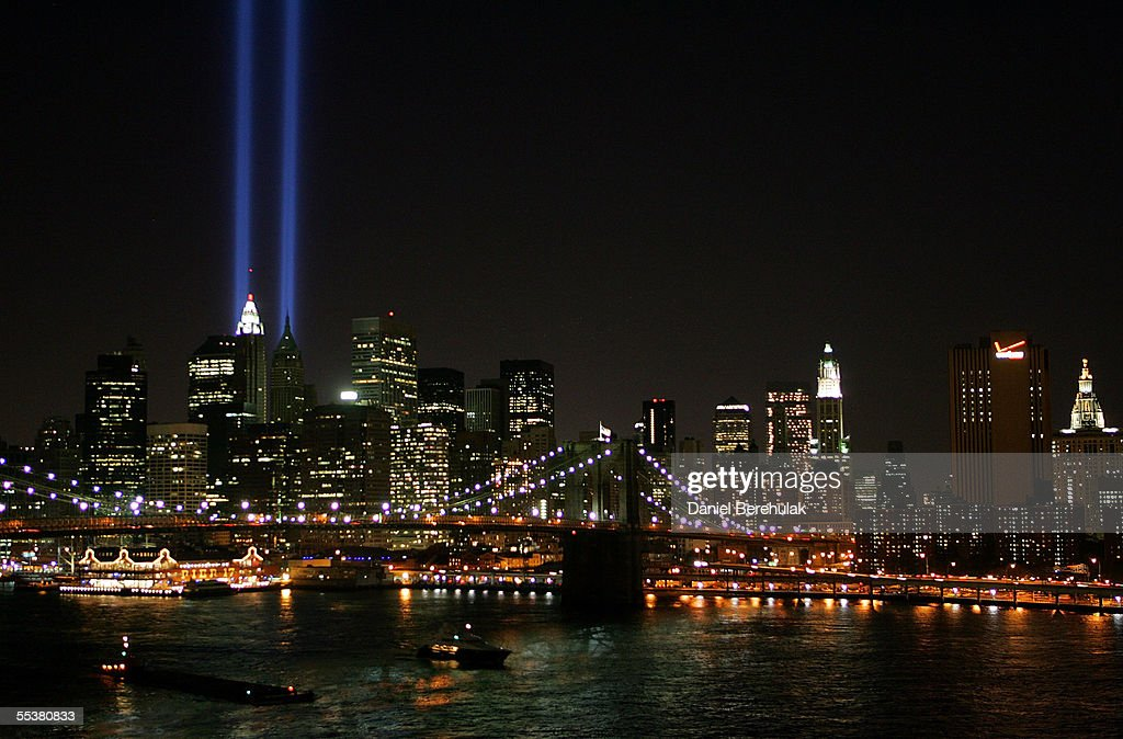 Beams of light shine into the sky behind the Brooklyn Bridge and above the Manhattan skyline on September 11, 2005 in New York City. The lights pay tribute to those who lost their lives when the World Trade Center was attacked four years ago.