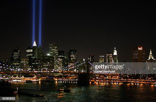 Beams of light shine into the sky behind the Brooklyn Bridge and above the Manhattan skyline on September 11 2005 in New York City The lights pay...