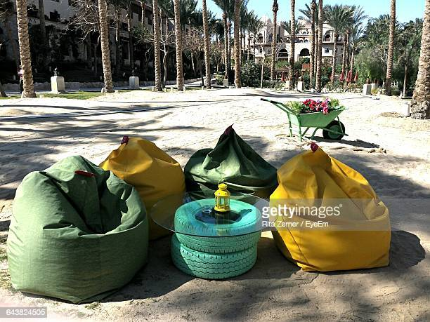 bean bags and glass on tires at beach - sacco photos et images de collection