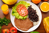 Bean, rice and steak with salad on wooden background