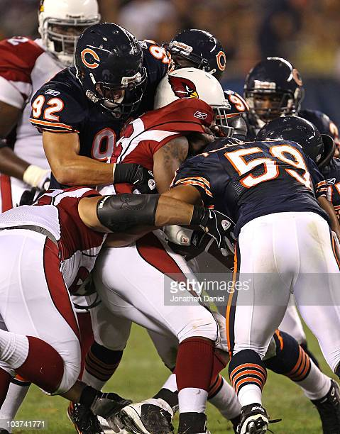 Beanie Wells of the Arizona Cardinals is tackled by Hunter Hillenmeyer Tommie Harris and Pisa Tinoisamoa of the Chicago Bears during a preseason game...