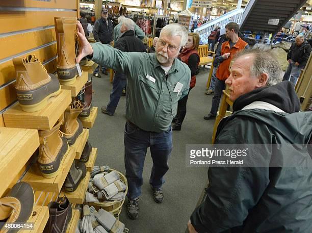 Bean's Steve James shows customer Barry Robichaud a pair of Bean boots at LL Bean in Freeport