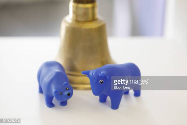 Bear and a bull toy figurines sit beside a bell following a news conference to announce the Deutsche Boerse AG earnings at the Frankfurt Stock...