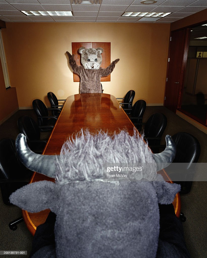Bear and bull looking at each other across conference room table : Stock Photo