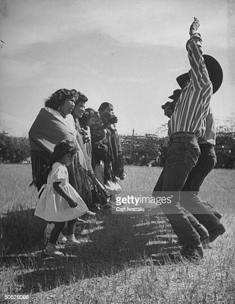 Bear dancing between proud braves and admiring maidens, joined by a small girl responding to the drum beat.