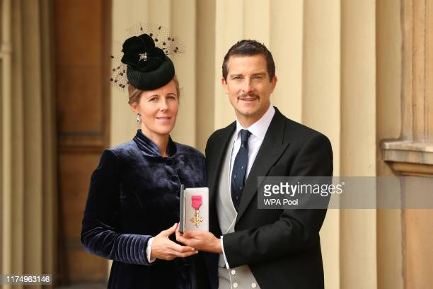 Bear Grylls poses with his wife Shara as he holds his OBE following an investiture ceremony at Buckingham Palace on October 10 2019 in London England