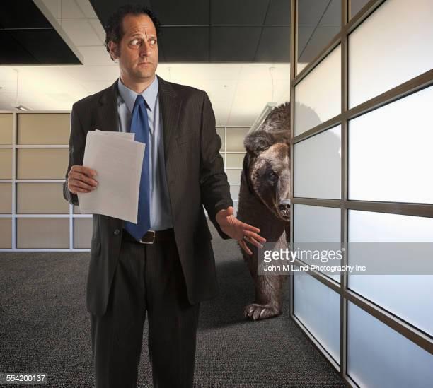 Bear stalking nervous businessman in office