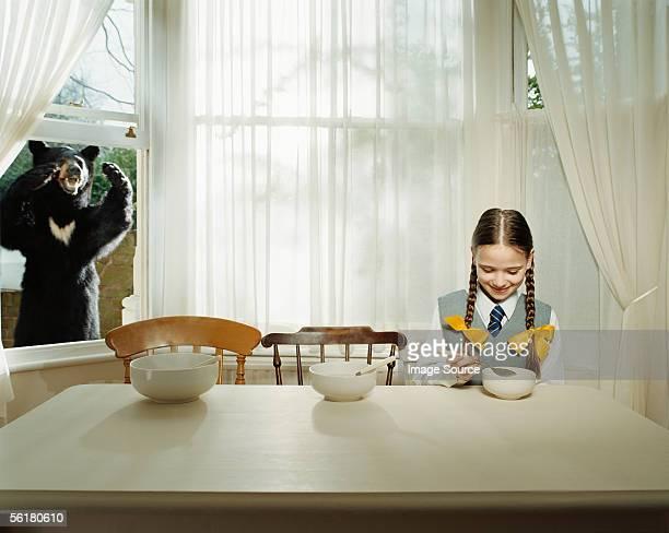 Bear watching girl eating
