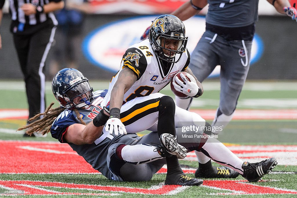Bear Woods #48 of the Montreal Alouettes takes down Bakari Grant #84 of the Hamilton Tiger-Cats during the CFL game at Percival Molson Stadium on September 7, 2014 in Montreal, Quebec, Canada.