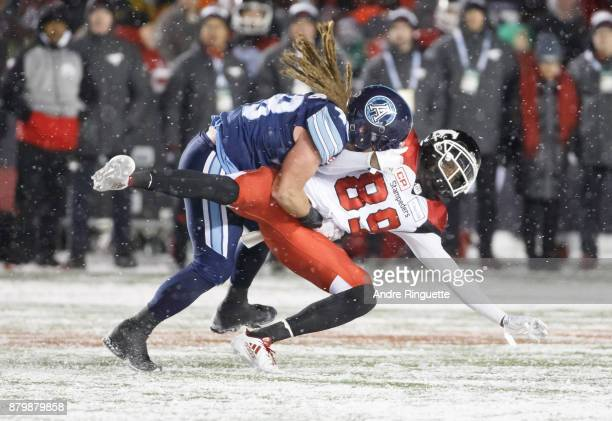 Bear Woods of the Toronto Argonauts tackles DaVaris Daniels of the Calgary Stampeders during the second half of the 105th Grey Cup Championship Game...