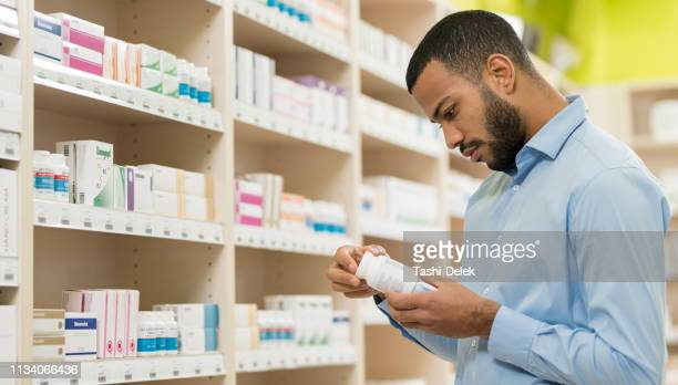 beard man choosing supplement in drugstore - vitamin stock pictures, royalty-free photos & images