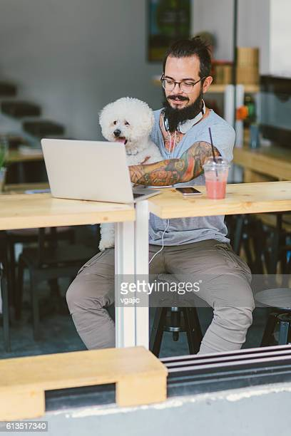 Beard Tattooed Man Sitting In Local Cafe With His Dog