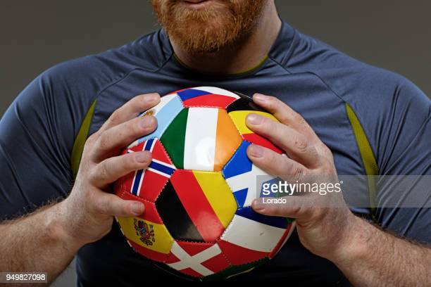 bearded aggressive redhead adult man football player holding a soccer ball covered in international flags - international team soccer stock pictures, royalty-free photos & images