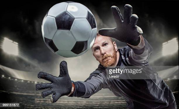 bearded aggressive redhead adult man goalkeeper saving a football in a floodlit soccer stadium - goalkeeper stock pictures, royalty-free photos & images