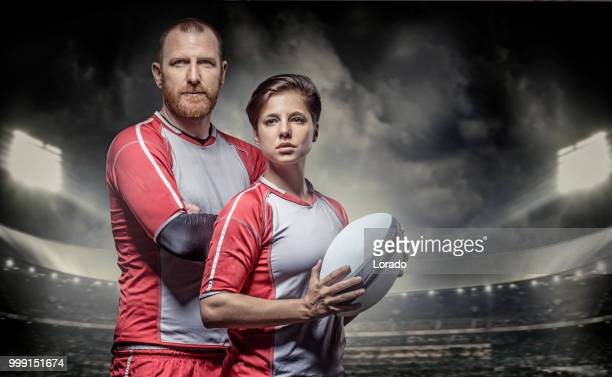 bärtige aggressive rothaarige erwachsenen mann rugby und schöne brünette spielerin in einem stadion mit flutlicht - frauen rugby stock-fotos und bilder