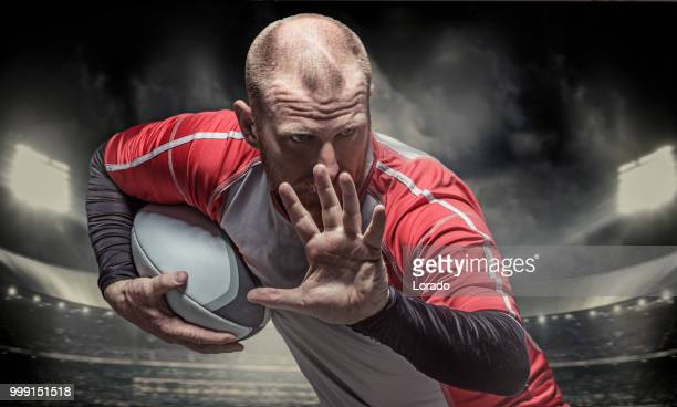 bearded aggressive redhead adult man rugby player holding a rugby ball in a floodlit stadium - rugby union stock pictures, royalty-free photos & images