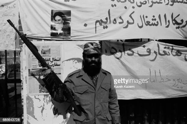 A bearded armed guard holding a German made G3 automatic assault rifle stands outside the American embassy where revolutionary slogans in support of...