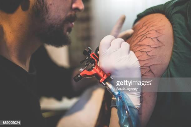 Bearded artist doing a tattoo