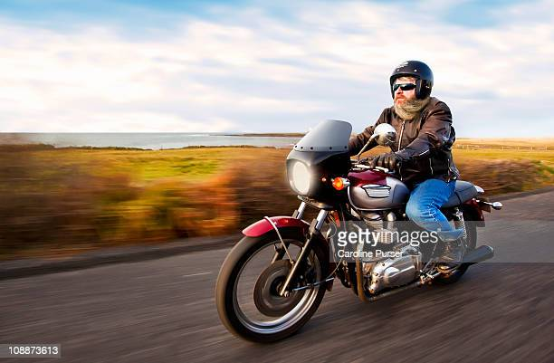 Bearded biker riding motorcycle next to ocean