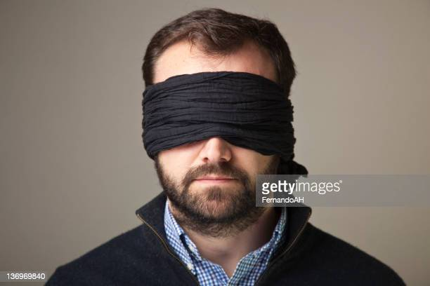 Bearded blindfolded man in a black jacket and blue shirt