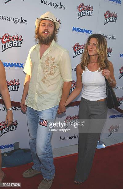 A bearded Brad Pitt holds hands with wife Jennifer Aniston while arriving at the premiere of Full Frontal