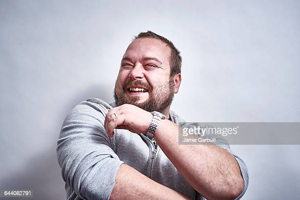 bearded british male laughing hysterically - lachen stock-fotos und bilder