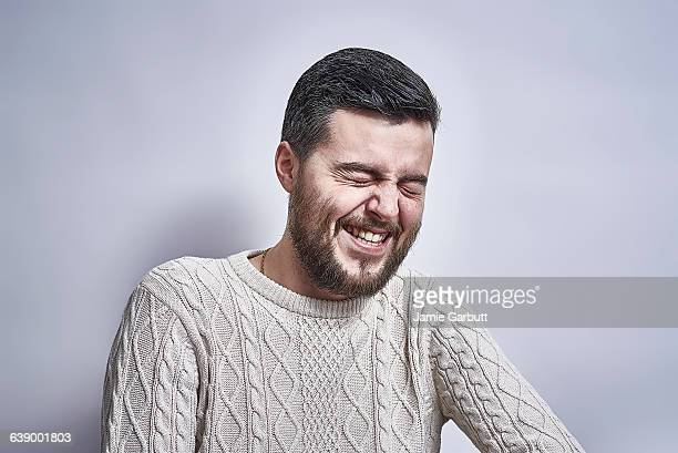 Bearded British male laughing with eyes closed