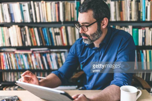 bearded business man checking checking business stats at digital tablet - creative director stock pictures, royalty-free photos & images