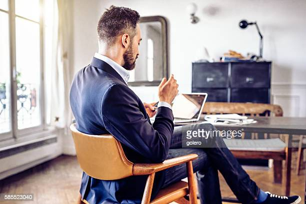 bearded business man looking at mobile in home office