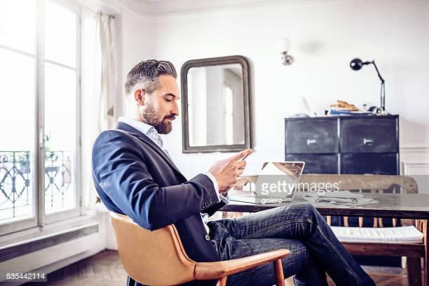 Bärtiger Geschäftsmann Lesung am Mobiltelefon in Büro