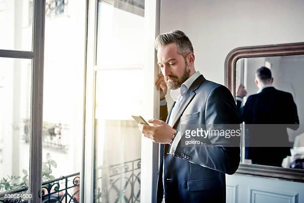 Barbu homme d'affaires lecture sur un smartphone à ouvrir la fenêtre